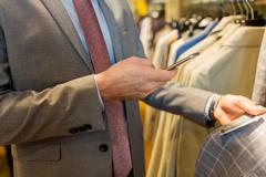 close up of man with smartphone at clothing store - stock photo