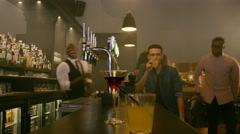 4K Time lapse man sitting at a busy bar while young crowd socialize around him Stock Footage