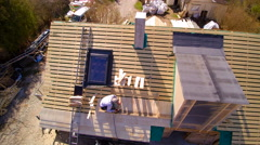 A roofer putting on the wooden shingles on the roof - stock footage
