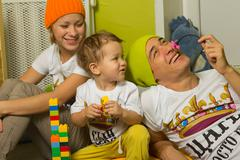Family playing with lots of colorful plasticconstruction blocks - stock photo