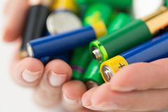 close up of hands holding alkaline batteries heap - stock photo