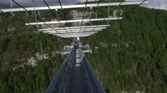 FPV entering suspended pedestrian skybridge, crossing deep ravine Stock Footage