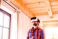 Man wearing virtual reality goggles standing in a kitchen - stock photo