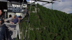 Man jump off on bungy rope from Skybridge, extreme attraction activity Stock Footage