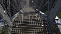 Look to ravine bottom through steel grate floor of gangway, suspended bridge - stock footage