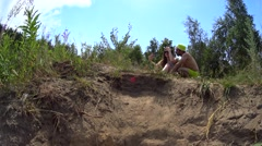 Cute couple taking selfie on summer country meadow lake shore, low angle shot Stock Footage