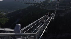 Tourists go across narrow steel suspended Sky Bridge, sunset view Stock Footage