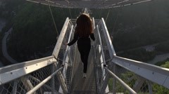 Follow long haired girl gracefully go downstairs at high suspended bridge Stock Footage