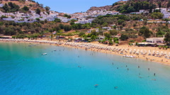 Tourists relax on sunny day at beach. Many people on holiday in Lindos , Greece Stock Footage