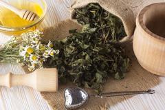Mortar, pestle, honey and herbal tea. Stock Photos