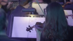 Violinist during a concert on stage playing the violin in the orchestra Stock Footage
