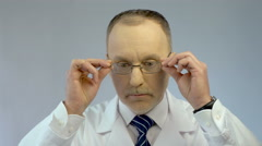 Chief physician putting on glasses, ready to examine patient, looking at camera Stock Footage