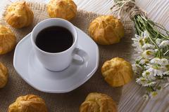Eclair, coffee cup and charmomile. - stock photo