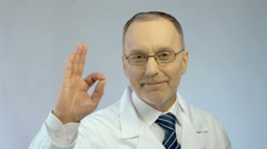 Male physician smiling, showing OK gesture, sure of successful treatment results Stock Footage