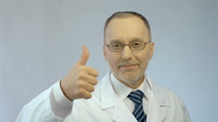 Male doctor smiling at camera, making thumbs-up hand sign, best medical aid Stock Footage