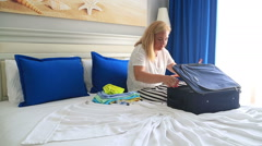 Woman packing suitcase in hotel room Arkistovideo