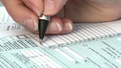Fill out your US tax return: tax form 1040, the young woman's hand writing Stock Footage