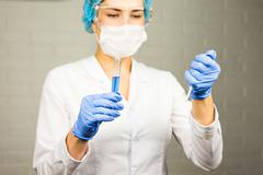 Close-up of glass tube with blue fluid in nurse hand during medical test - stock photo