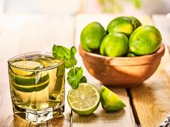 On wooden boards is glass with green mohito drink. - stock photo