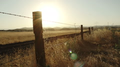 Barbed wire fence country roadside at sunrise in Fresno California Stock Footage