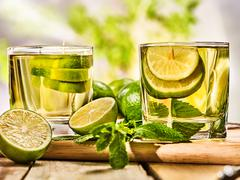 On wooden boards two mohito drink glass and half lime. - stock photo