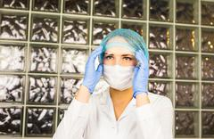 medical procedures and hygiene concept - Doctor wearing glasses, surgical mask - stock photo