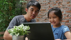 4K : Asian man teaching his daughter for using computer laptop - stock footage