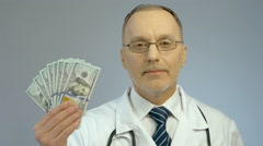 Doctor holding bundle of dollars, paid medicine, expensive health care services Stock Footage