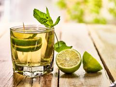 On wooden boards is mohito drink glass and half lime. - stock photo