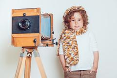 Little boy standing near the camera on a white background - stock photo