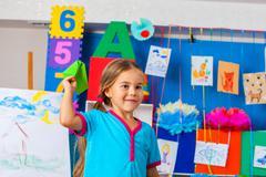 Girl kids holding origami airplane in kindergarten . - stock photo