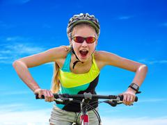 Bikes cycling girl wearing helmet rides bicycle aganist blue sky. - stock photo