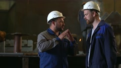 Engineer in hardhat explaining the process to his collegue in front of welding Stock Footage