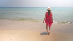 Young and happy pregnant woman walkin into the sea water at a sunny and windy Stock Footage