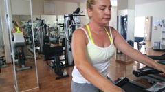 Woman Training On Exercise Bicycle In The Gym Stock Footage