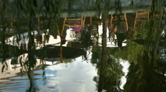 Terrace bar with silhouette people seen in the reflection in water canal Stock Footage