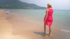 Expectant mother in swimsuit and red tunic walking along the water edge Stock Footage