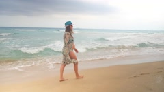 Stylish pregnant woman in swimsuite and tunic walking on a sandy beach along sea Stock Footage