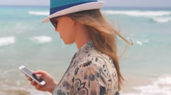 Clos up handheld shoting of a caucasian woman walking along the sea with her Stock Footage