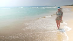 Smiling pregnant woman walking on a beach in swimwear, tunic and blue hat Stock Footage