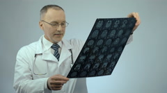 Happy smiling doctor checking MRI brain scan, satisfied with treatment results Stock Footage