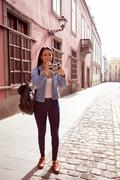 Cute young girl taking a picture in a narrow paved street with old pink build - stock photo