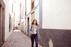 Pretty young girl hurrying down a narrow paved street looking at the camera w - stock photo