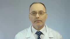 Experienced look of serious male physician, professional medical aid at clinic Stock Footage