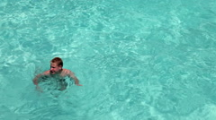 The boy, the teenager, swimming in blue transparent water of the sea and waves a Stock Footage