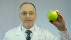 Male nutritionist showing fresh apple at camera, offering patient healthy diet Stock Footage