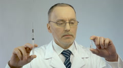 Doctor holding syringe and ampoule, prescribing effective medication to patient - stock footage