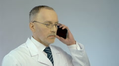 Doctor using mobile phone, dialing number, calling patient to arrange meeting - stock footage