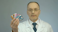 Bunch of pills in doctor's hand, promotion of pharmaceutical industry products Stock Footage