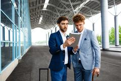 Picture of  two young businessmen talking on station background and holding - stock photo